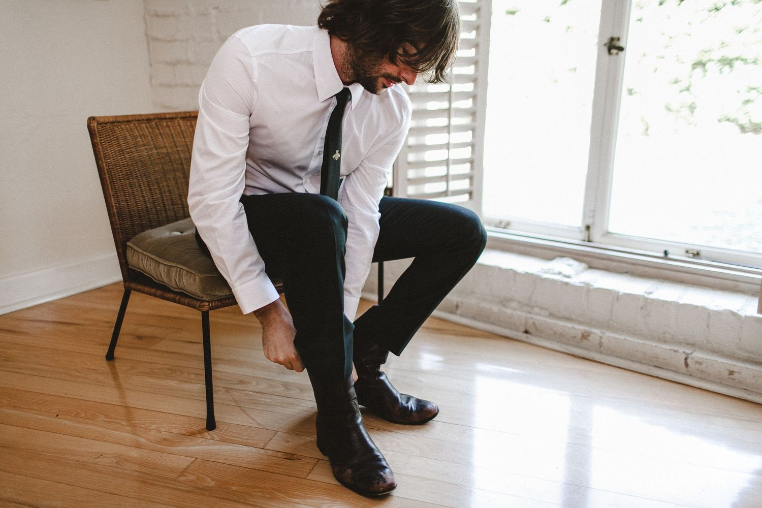 groom putting on shoes sitting next to window