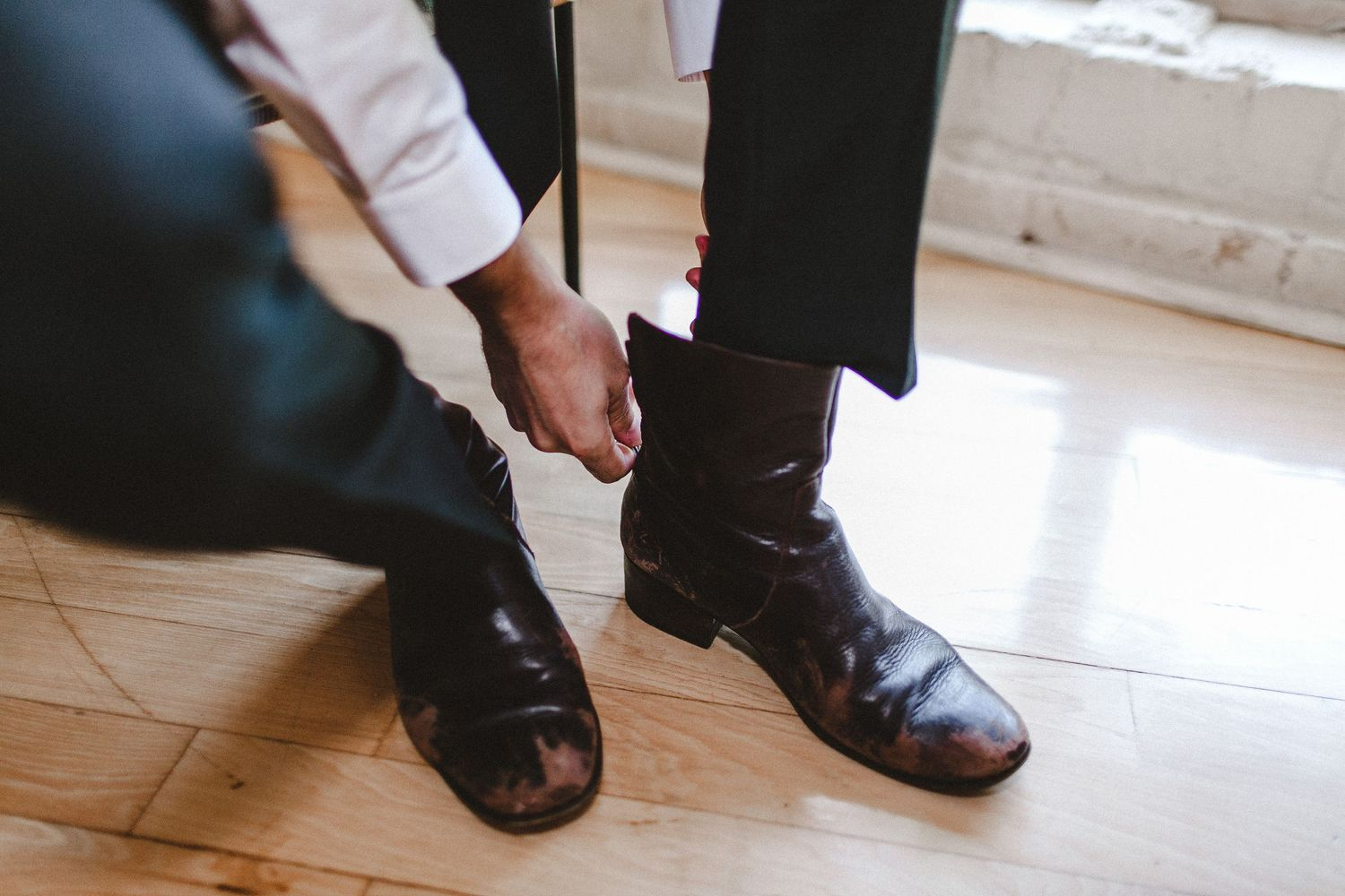 close photo of groom putting on boots for wedding day
