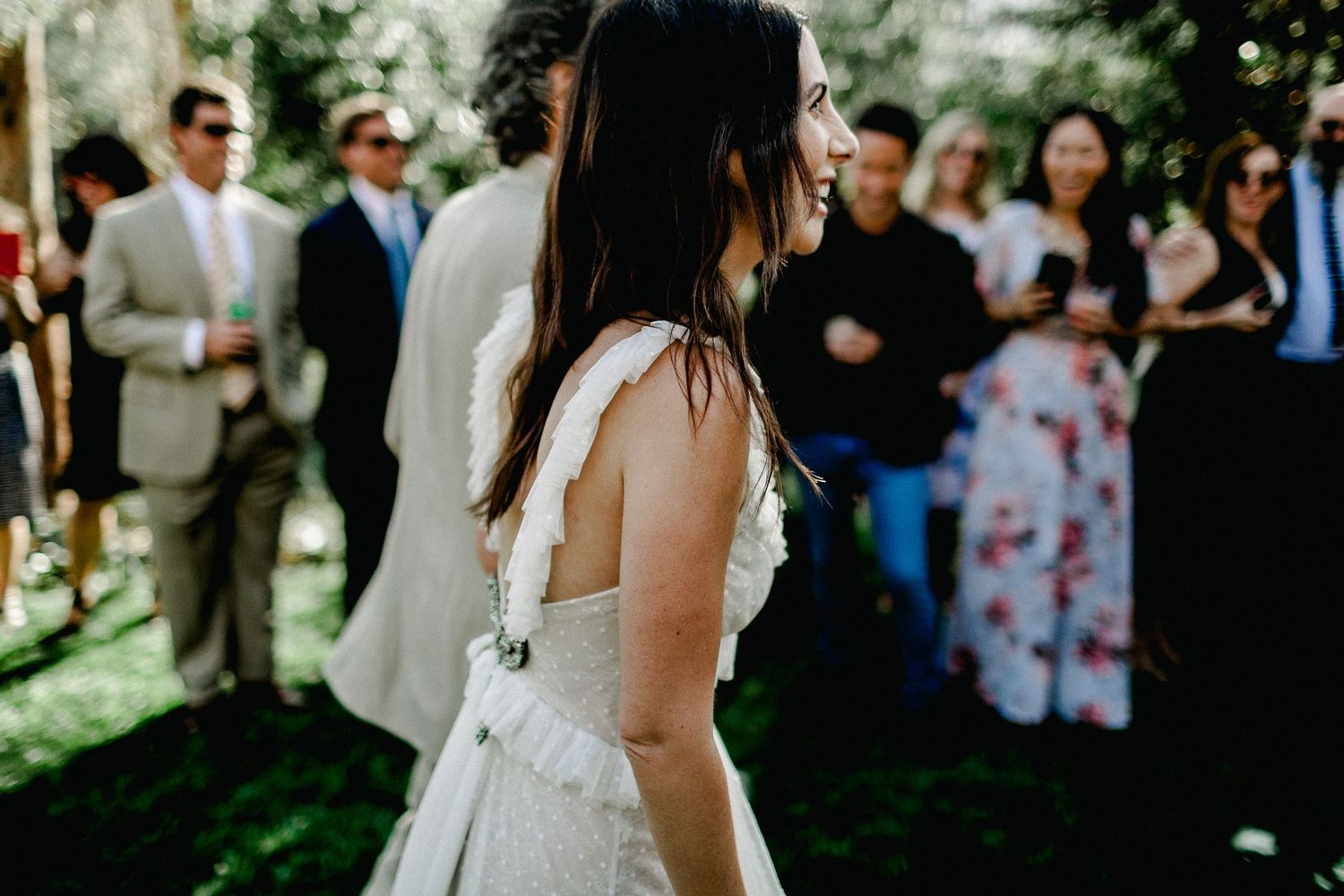 side shot of bride walking down and seeing guests in her wedding dress