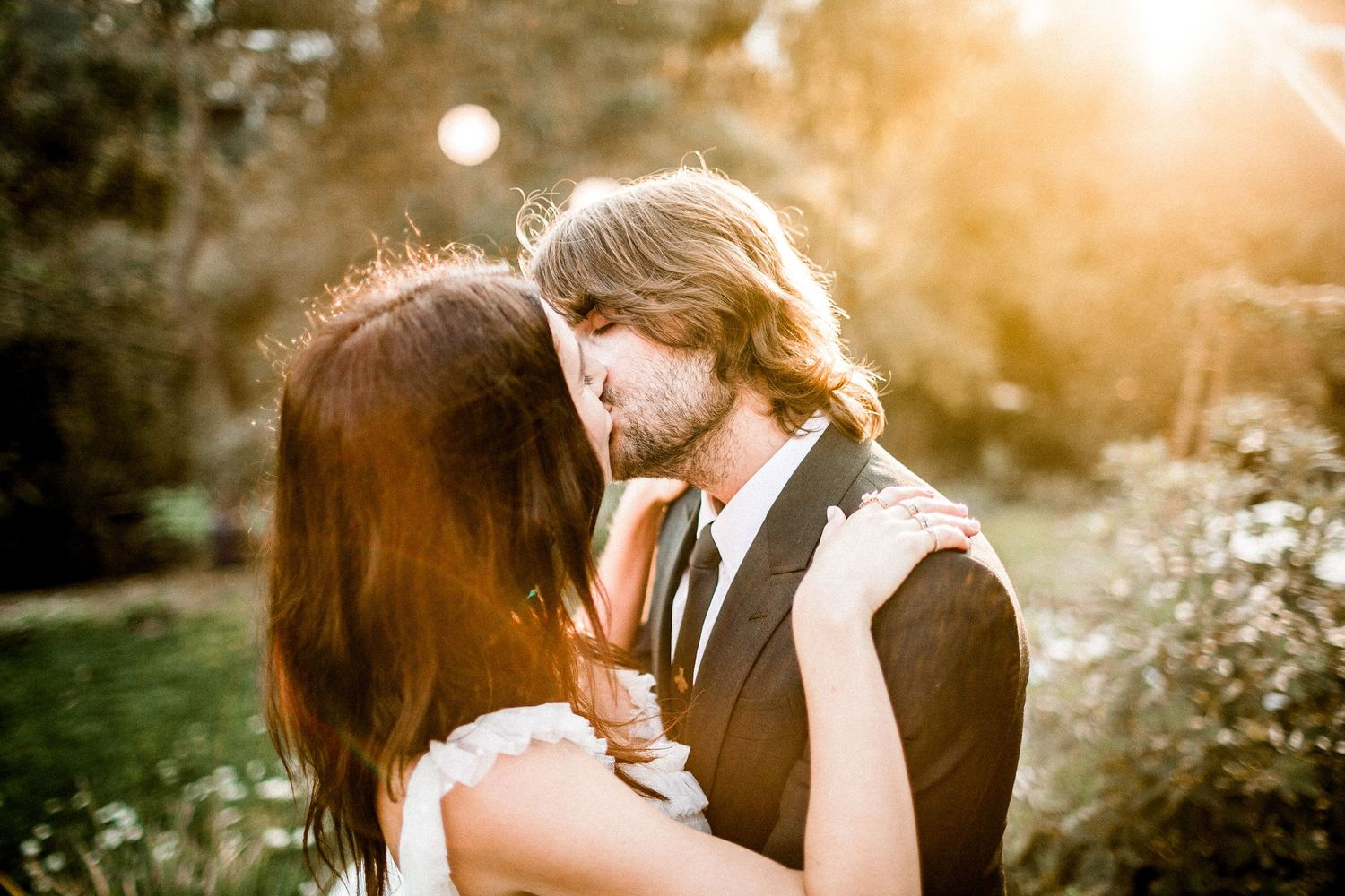 bride kissing groom with golden hour lighting behind