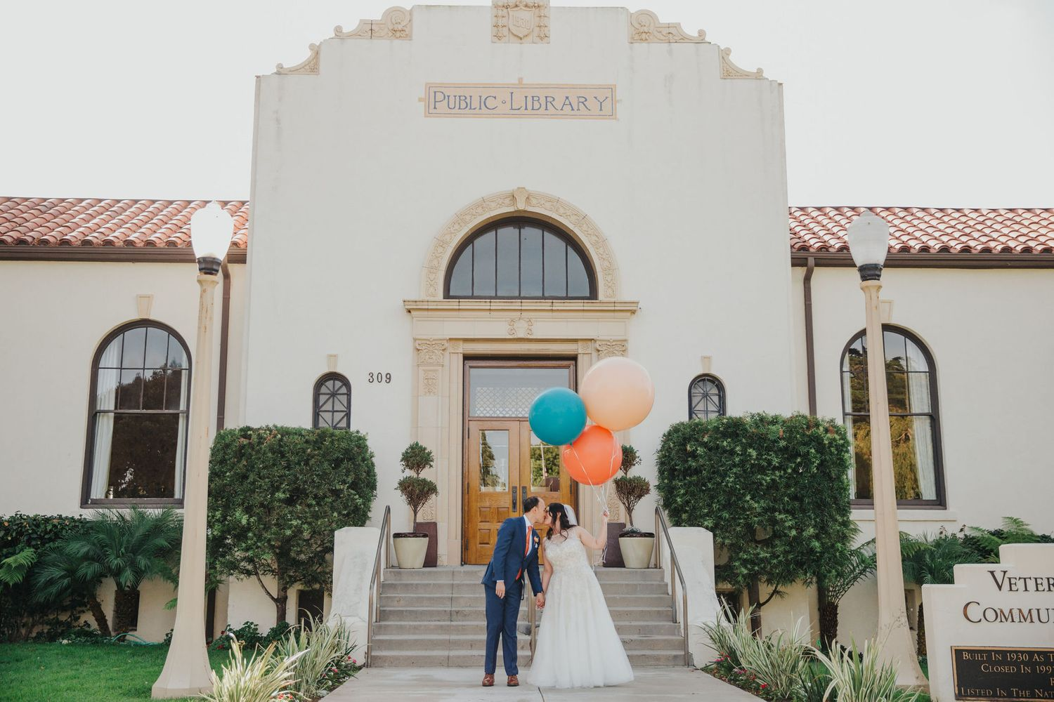 bride & groom with balloons in front of the redondo beach historic library