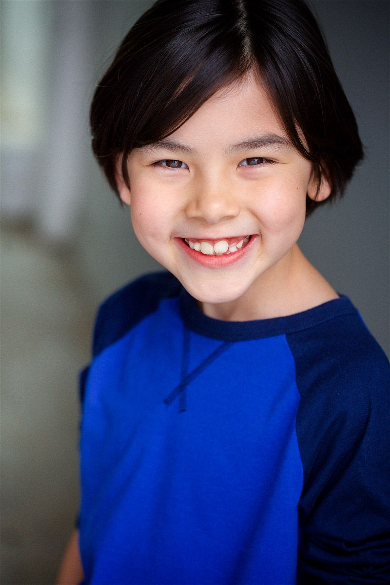 headshots nyc of adorable kid actor smiling in blue shirt