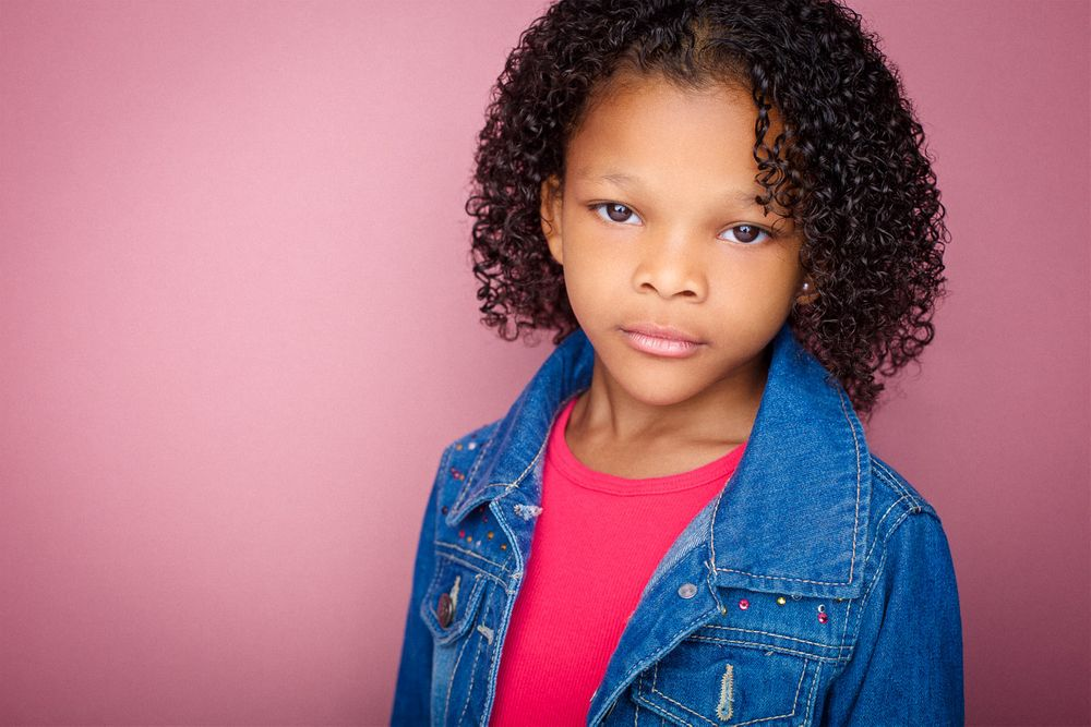 headshots nyc of tough looking kid actor with curly hair against pink backdrop