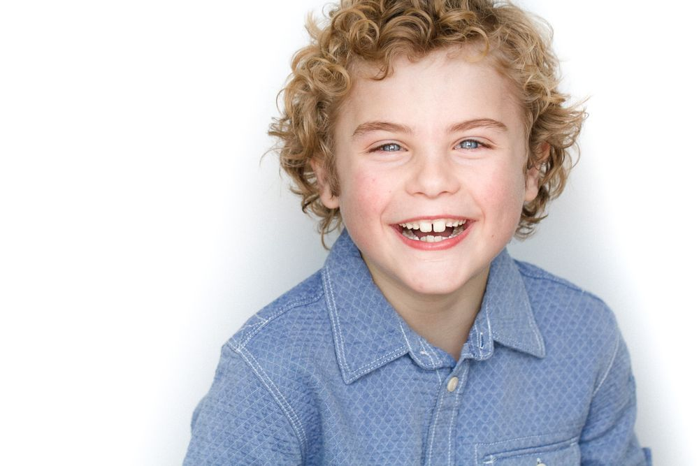 headshots nyc of kid actor with blonde curly hair laughing