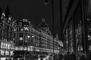 London Harrod's lit up at night reflected in a window
