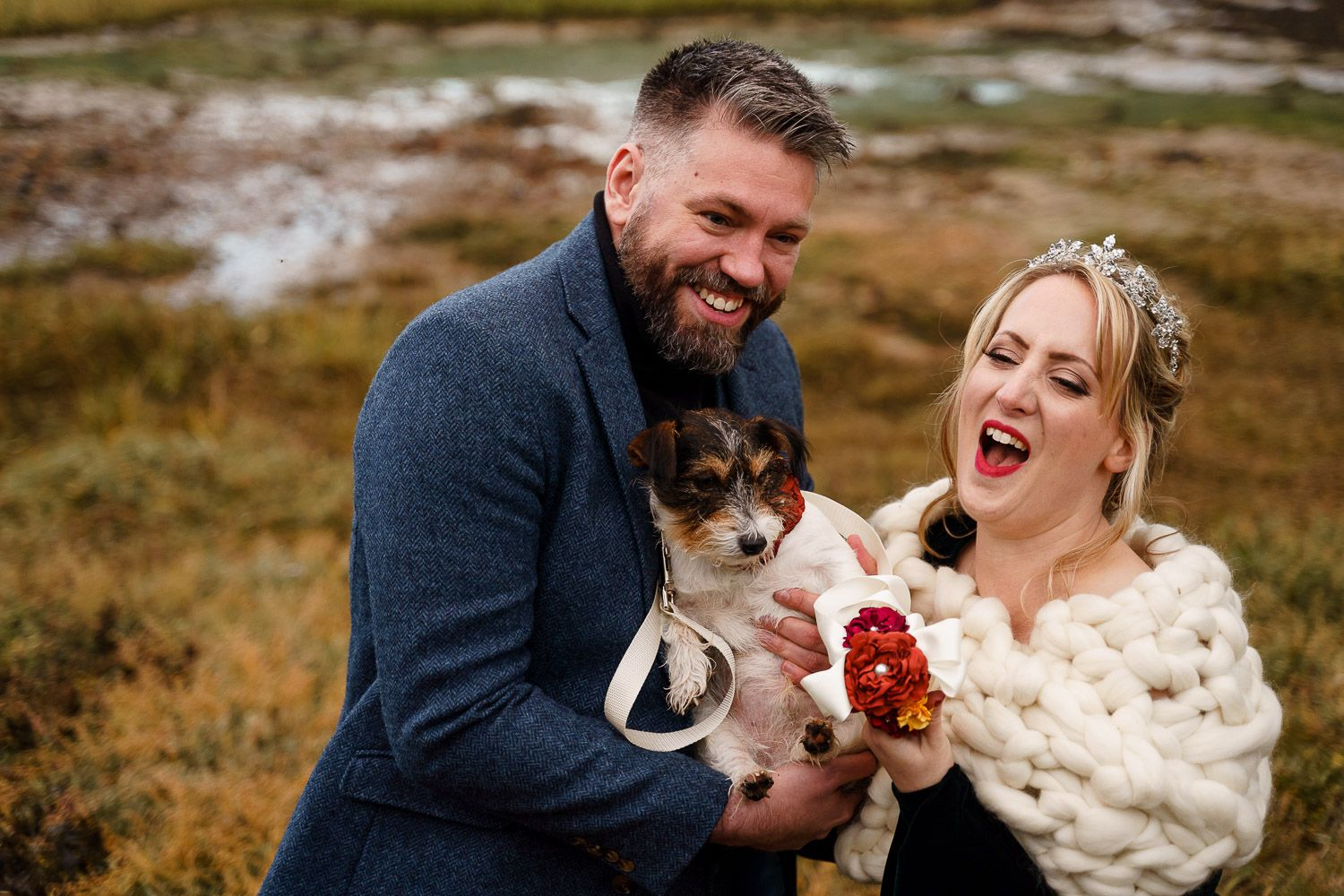 Bride and groom laugh as they hug their dog at their wedding. Top 10 dog-friendly wedding tips.