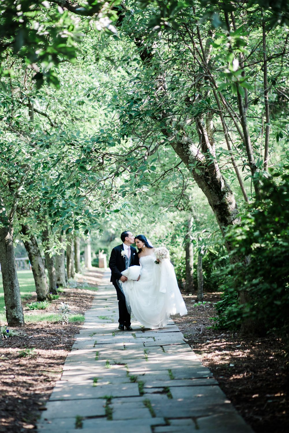 Bride and groom walk down a stone path at the New Jersey Botanical Gardens