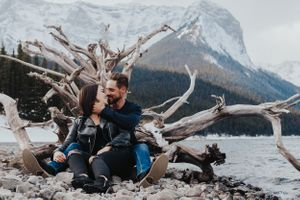 Couple kiss in front of driftwood at engagement photo session in Kananaskis