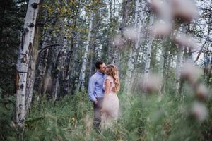 Man kisses fiance on the cheek in field in Alberta