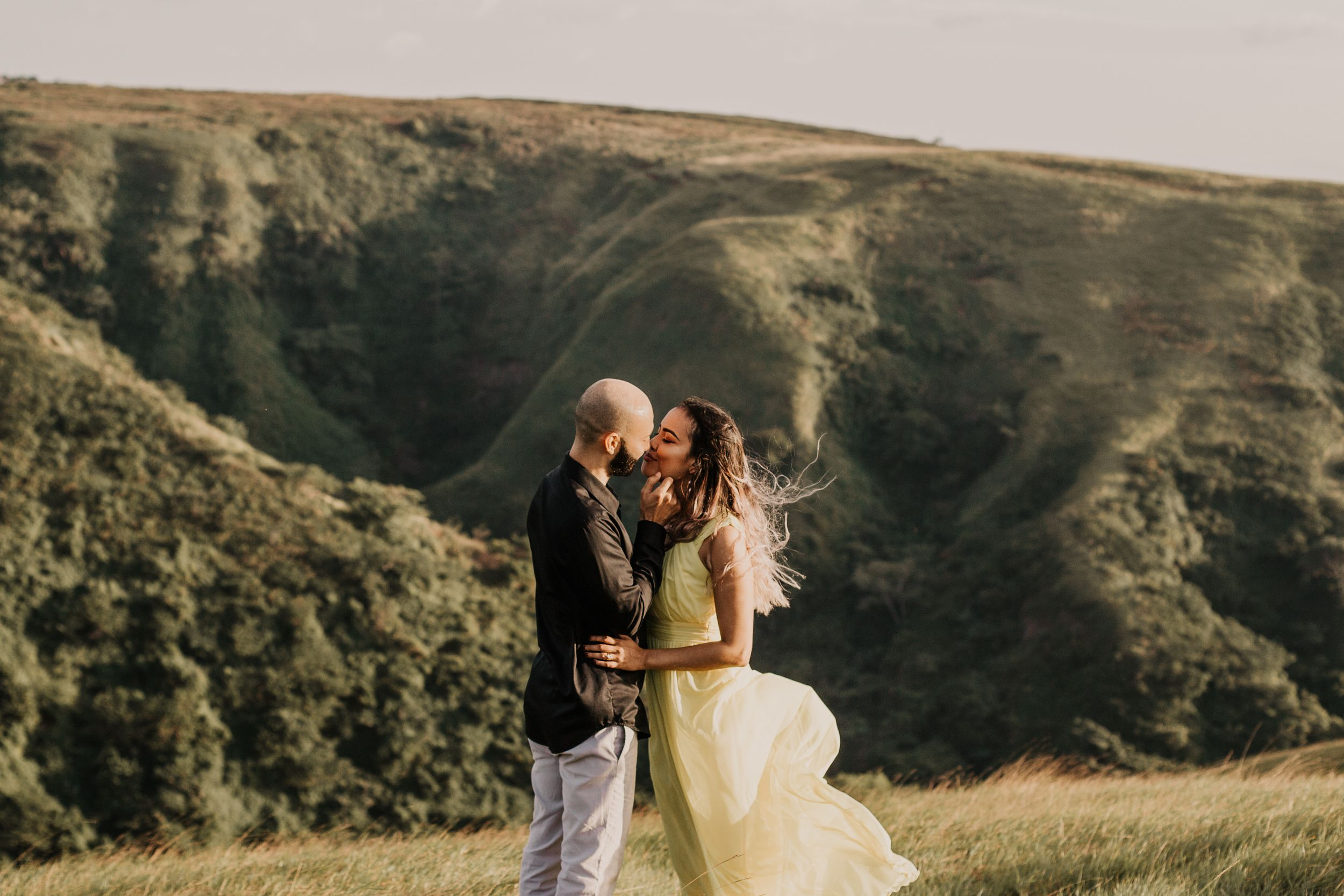 Girls hair blows in the wind as husband goes in to kiss her in front of beautiful view