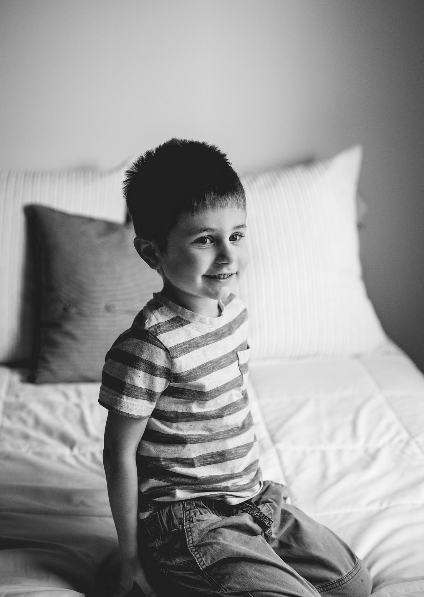 little boy kneeling on bed and smiling