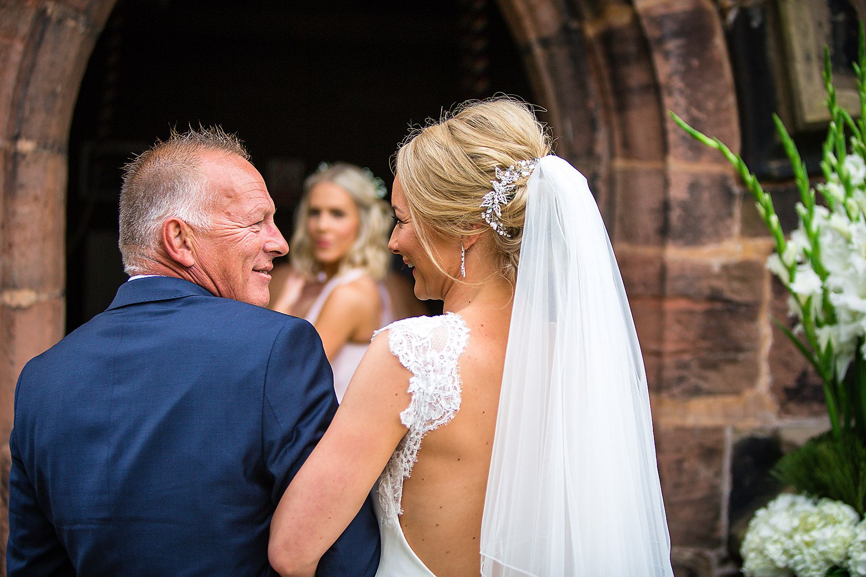 Father of brides looks proudly at his daughter, watched by bridesmaids at the church entrance