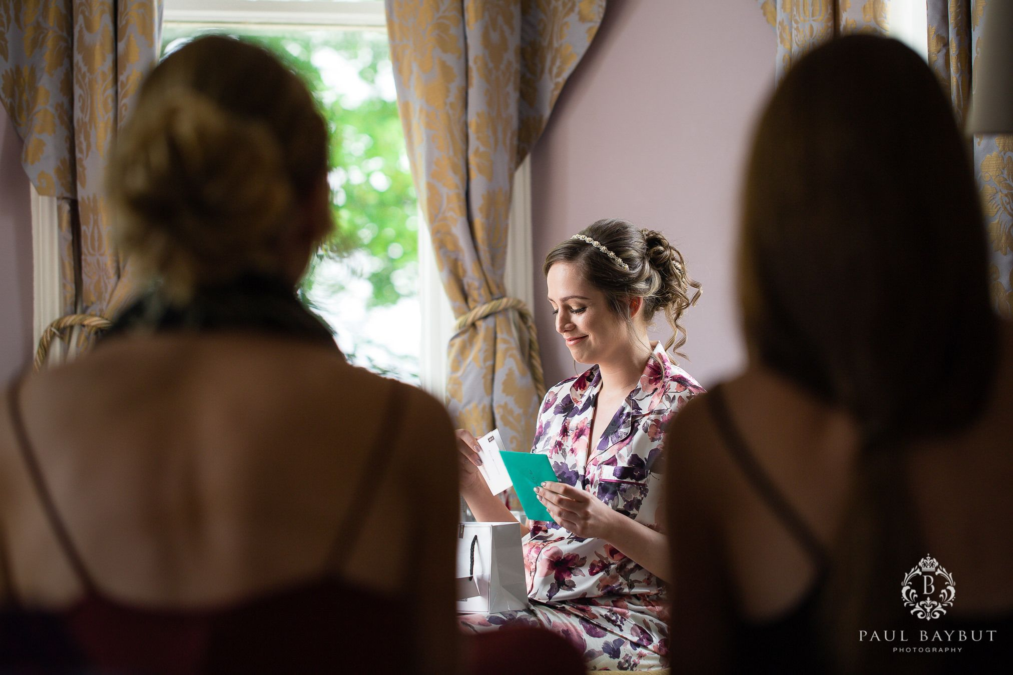 Bridesmaids watch a delighted bride as she reads a message in a card during bridal prep at Hollin House Hotel