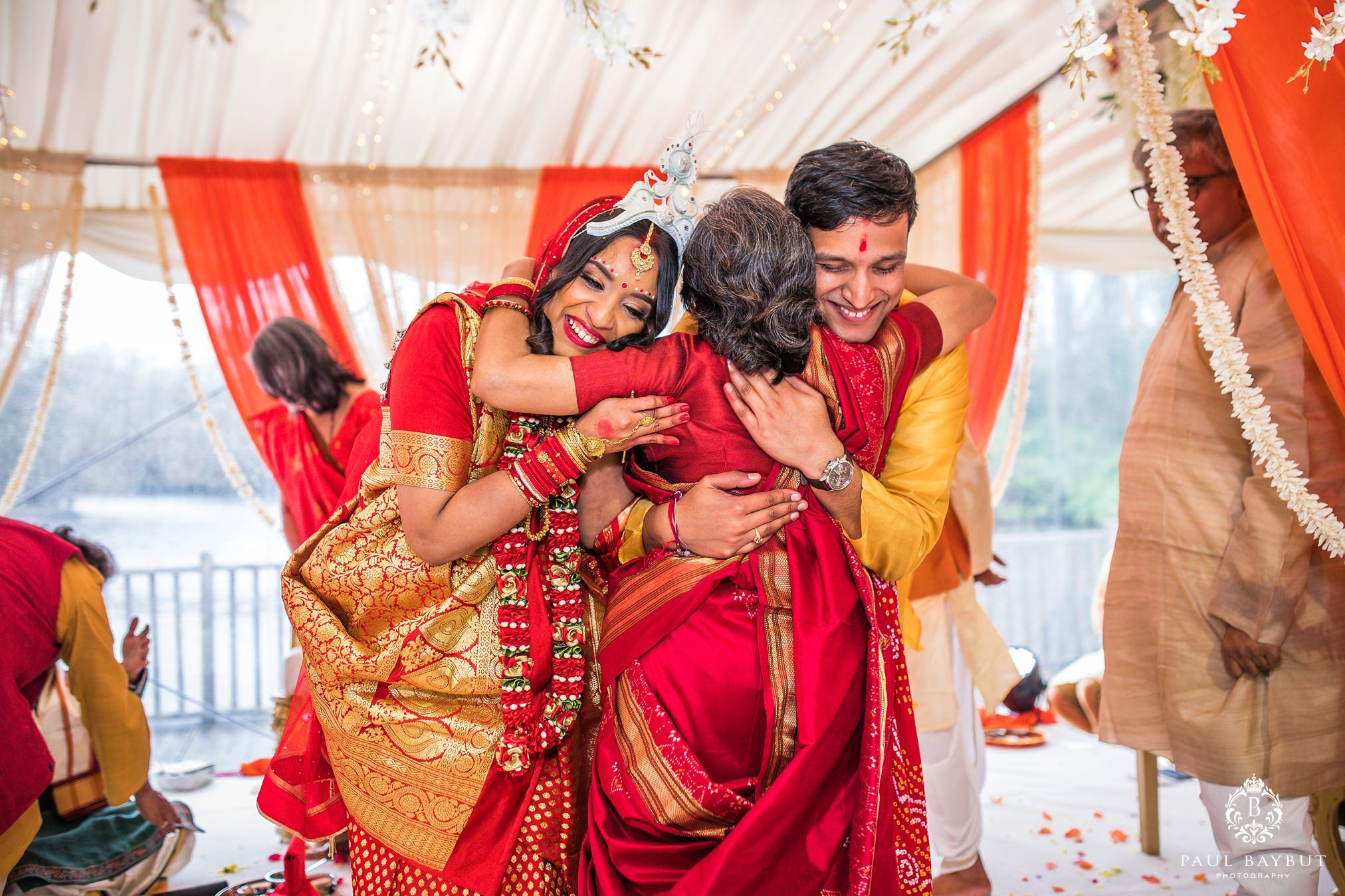 Newly weds both hug a female guest during their asian wedding ceremony at Thornton Manor Marquee