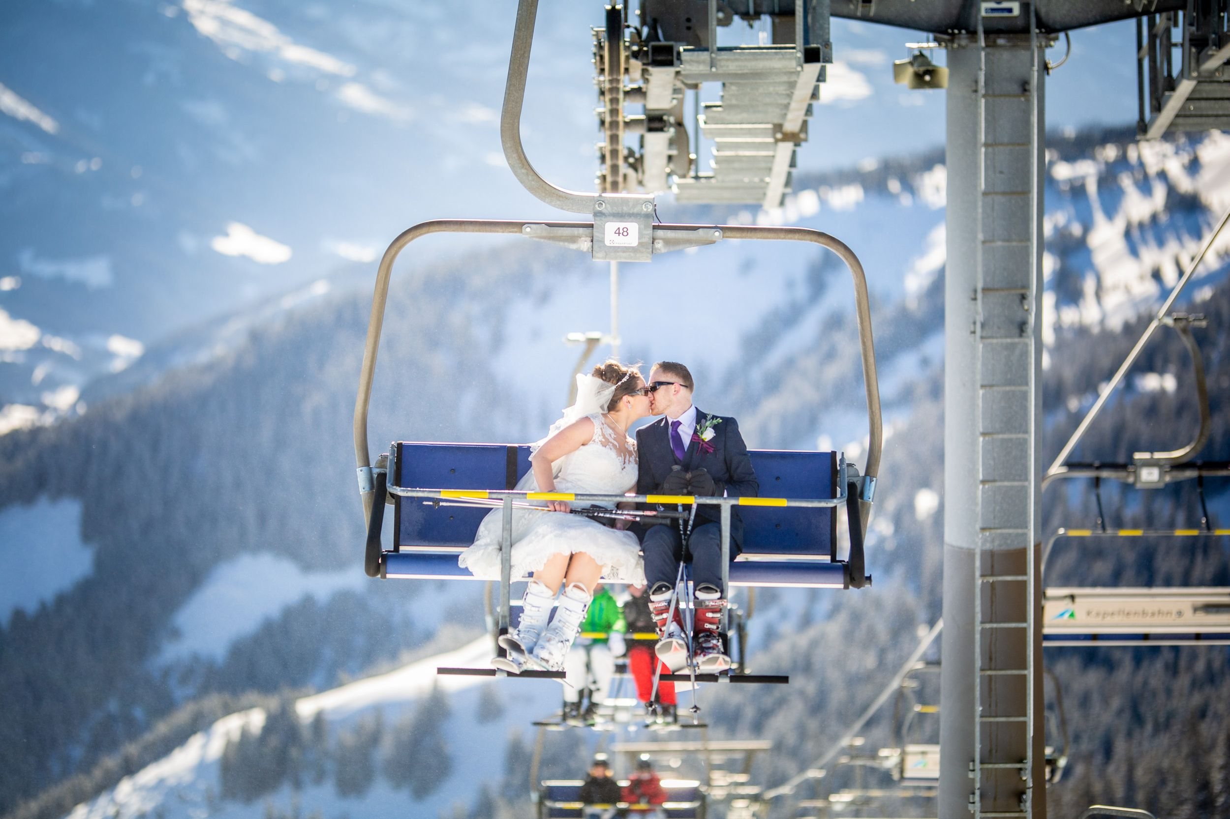 Wedding couple kisses on ski lift