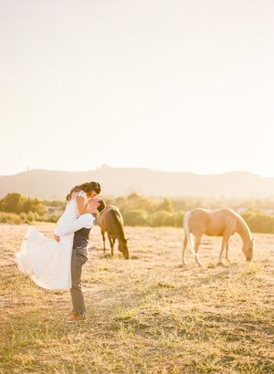 Bride and groom kissing in a field at sunset with horses at Pepper Tree Ranch wedding