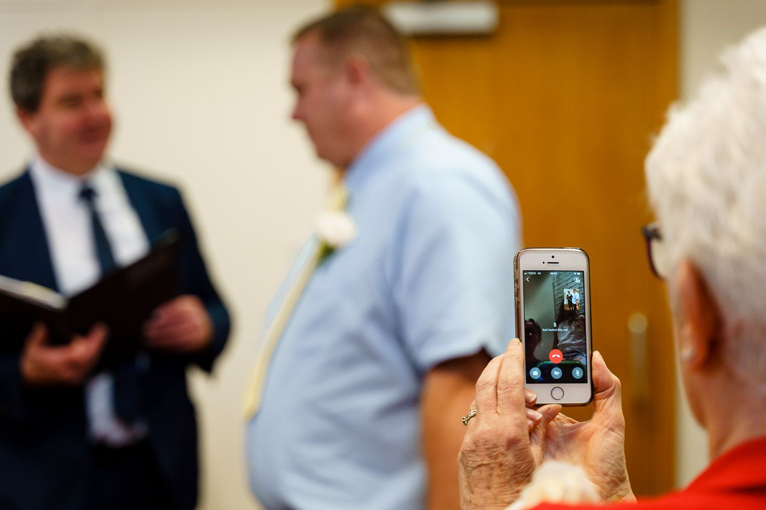 Mother of the bride holds up an iphone at Southampton Registry Office so relatives in New Zealand can watch the ceremony