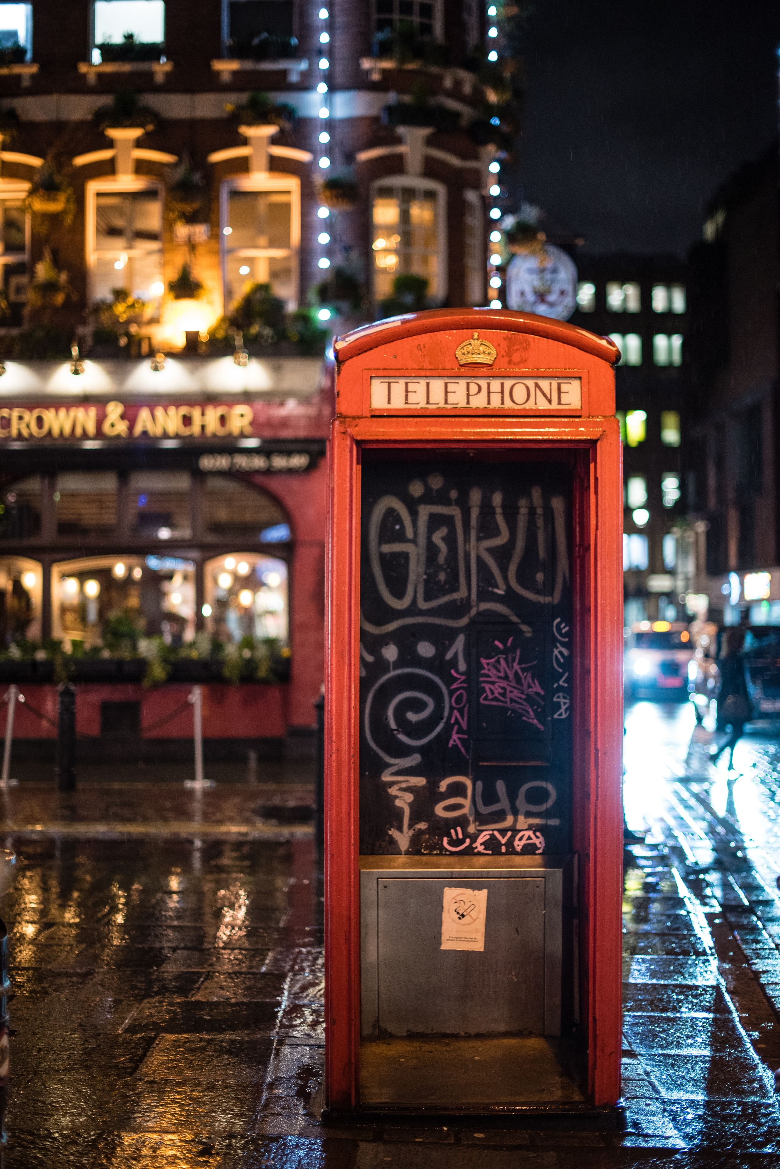 London's famous red telephone booth on a rainy night at Crown & Anchor