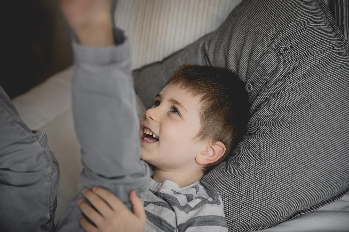 little boy laughing on a bed