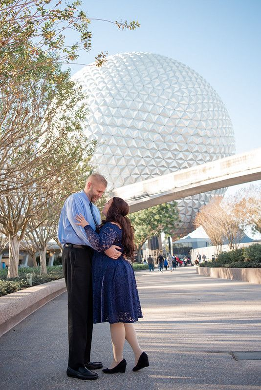A couple standing in front of Spaceship Earth at Walt Disney World's Epcot in Orlando FL