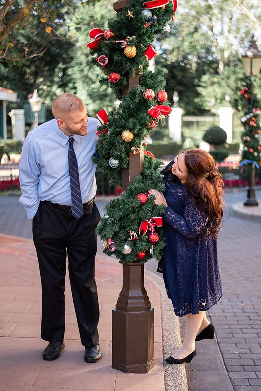 A couple standing against a lamppost with Christmas decor at the UK Pavilion at Walt Disney World's Epcot in Orlando FL