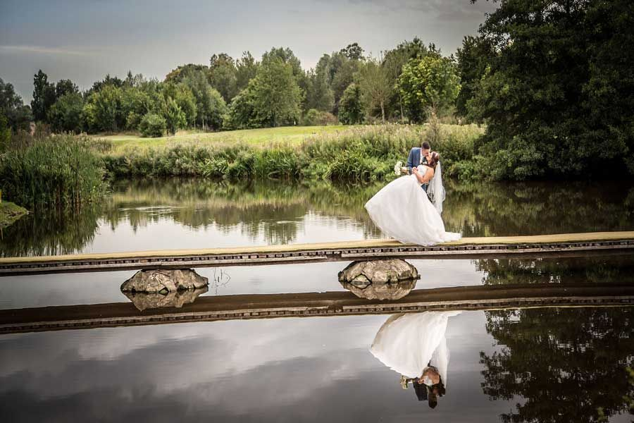 Bride and groom on boardwalk over river
