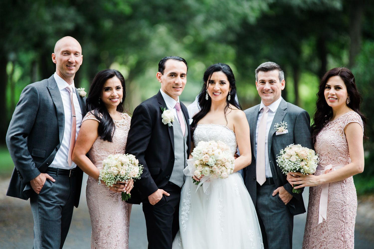 Wedding party with bridesmaids in blush lace and groomsmen in grey suits