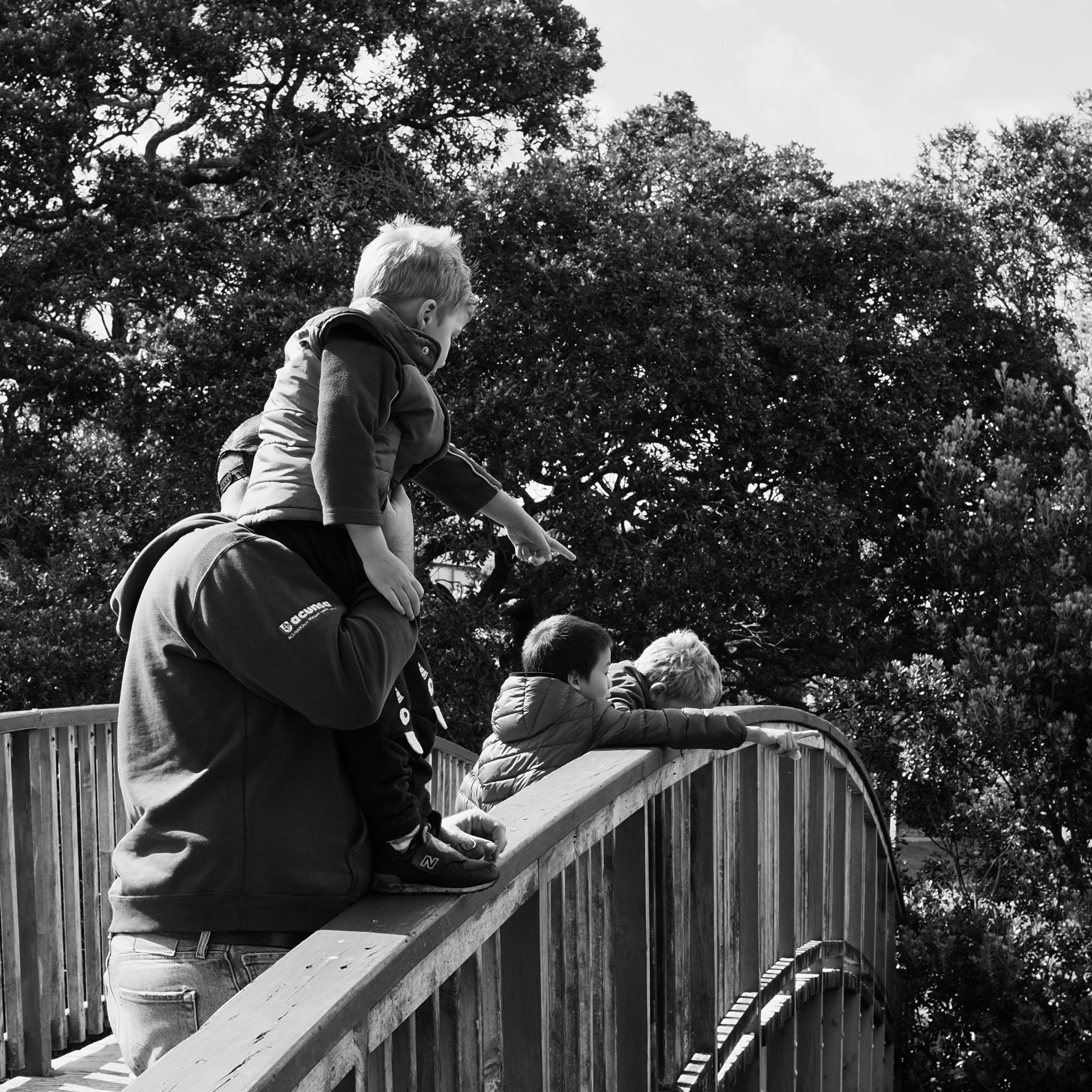 A black and white photo of the boys standing on a bridge pointing down at things floating in the estuary