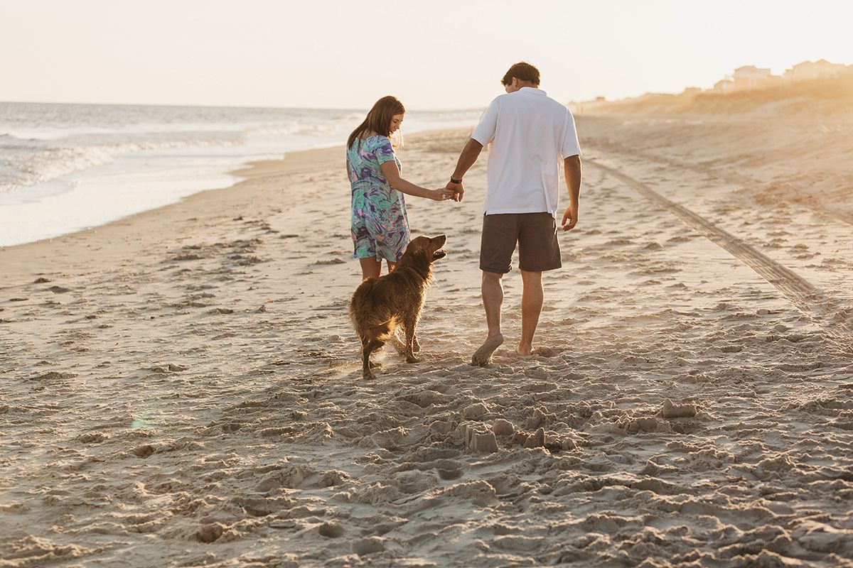 couple walking on the beach with dog in Atlantic Beach, NC