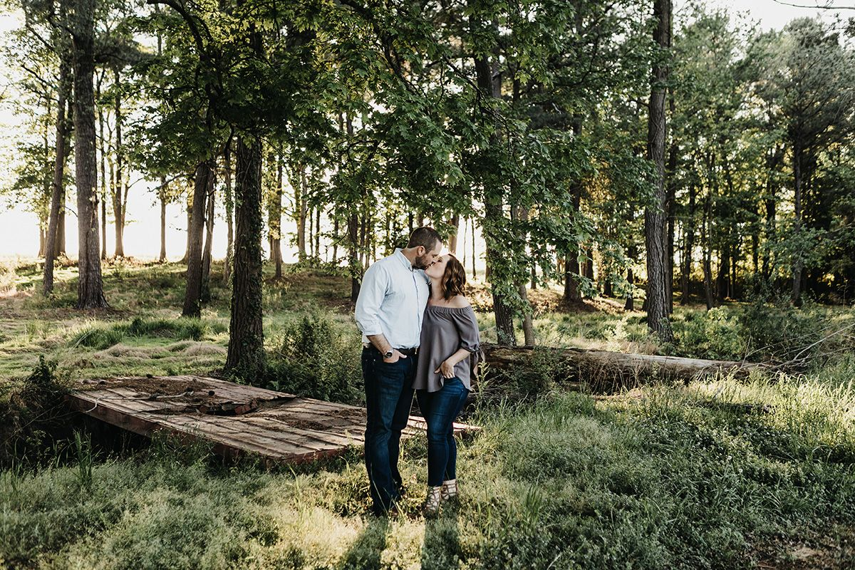 couple kissing in forest at May-Lew Farm in Farmville, NC