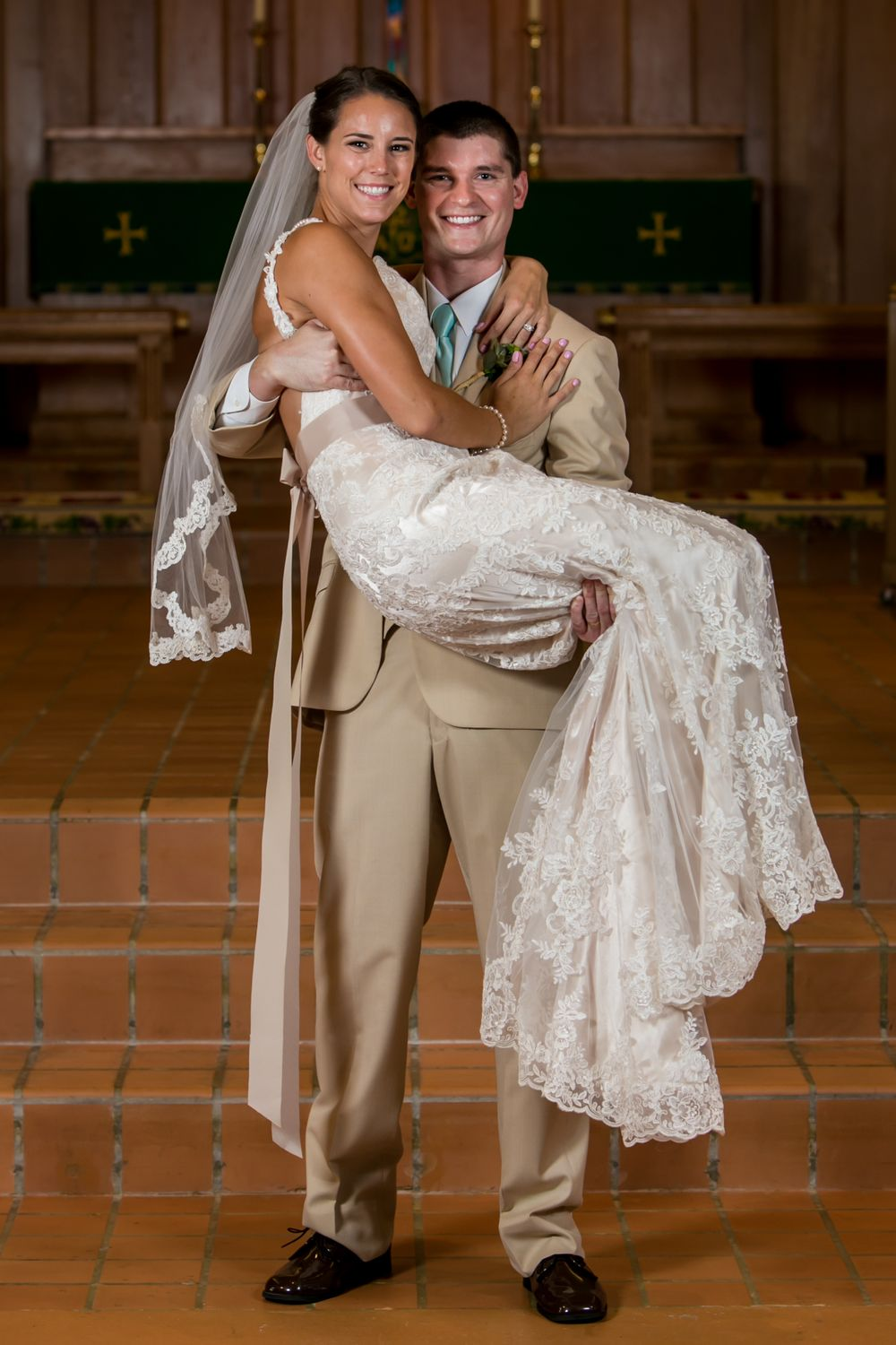 Groom Mike scoops up bride Alex following their wedding ceremony at Incarnation Lutheran Church in Columbia, SC