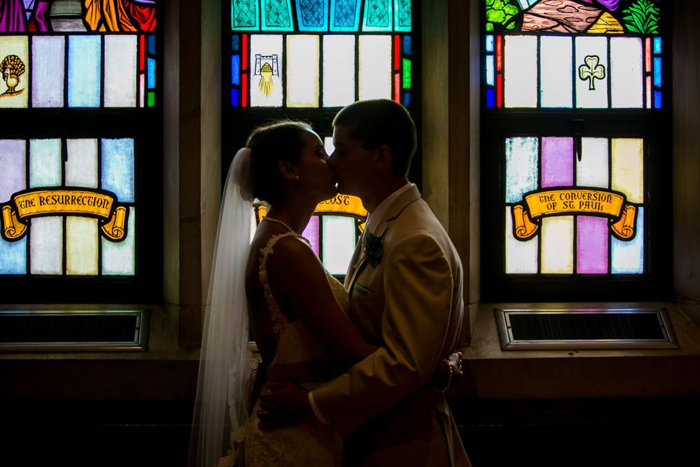 Alex & Michael kiss in front of stained-glass after their wedding at Incarnation Lutheran Church in Columbia, SC.