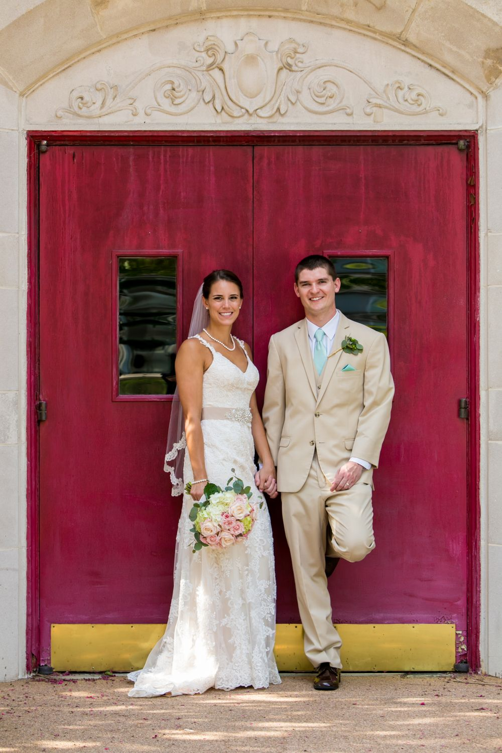 Alex & Michael kiss in front of the front red door after their wedding at Incarnation Lutheran Church in Columbia, SC.
