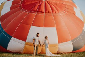 bride-groom-standing-in-front-of-hot-air-balloon-indianola-iowa-raelyn-ramey-photography