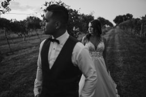 bride-and-groom-standing-in-vineyard-carper-winery-norwalk-iowa-raelyn-ramey-photography