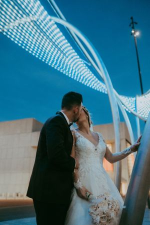 bride-groom-kissing-at-night-with-lights-downtown-desmoines-iowa-raelyn-ramey-photography