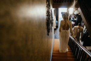 bride-walking-down-old-victorian-staircase-vinton-iowa-raelyn-ramey-photography
