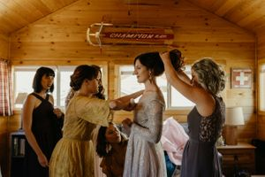 bridesmaids-helping-bride-get-ready-lupine-village-grand-lake-colorado-raelyn-ramey-photography