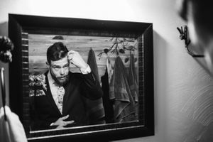 groom-getting-ready-in-mirror-lupine-village-grand-lake-colorado-raelyn-ramey-photography
