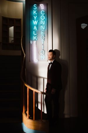 groom-standing-next-to-neon-light-downtown-desmoines-iowa-raelyn-ramey-photography