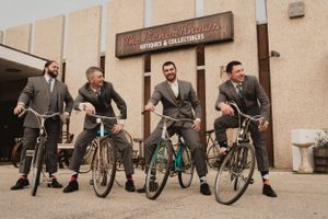 groomsmen-sitting-on-old-vintage-bikes-decades-event-center-desmoines-iowa-raelyn-ramey-photography