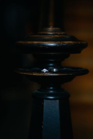 detail-shot-of-wedding-rings-on-old-newel-post-victorian-vinton-iowa-raelyn-ramey-photography
