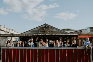 bride-groom-and-wedding-party-cheers-at-el-bait-shop-desmoines-iowa-raelyn-ramey-photography