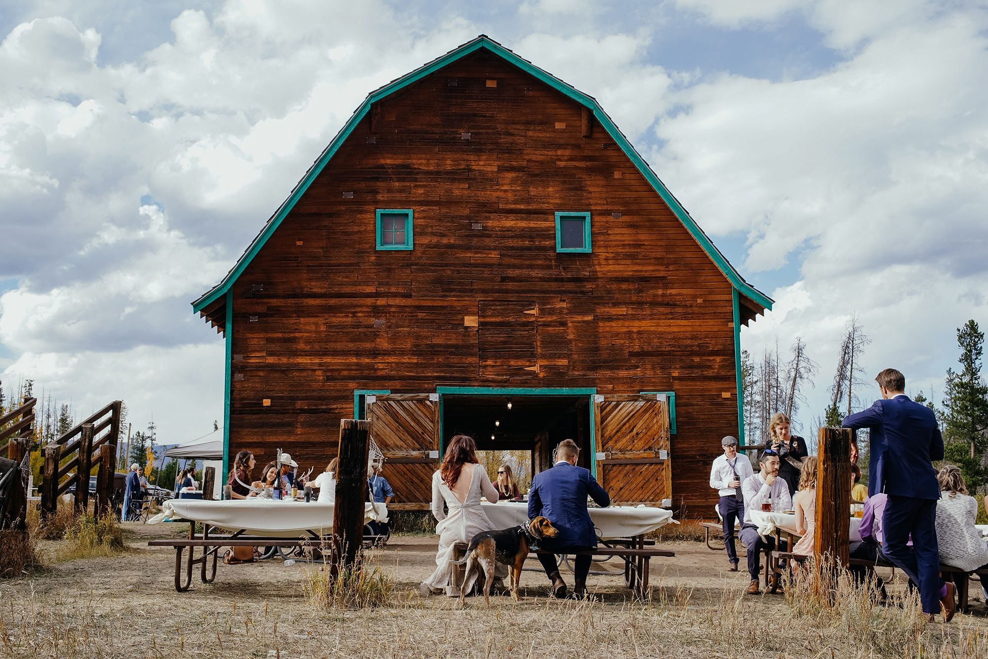 bride-groom-sitting-down-to-eat-outside-double-a-barn-grand-lake-colorado-raelyn-ramey-photography