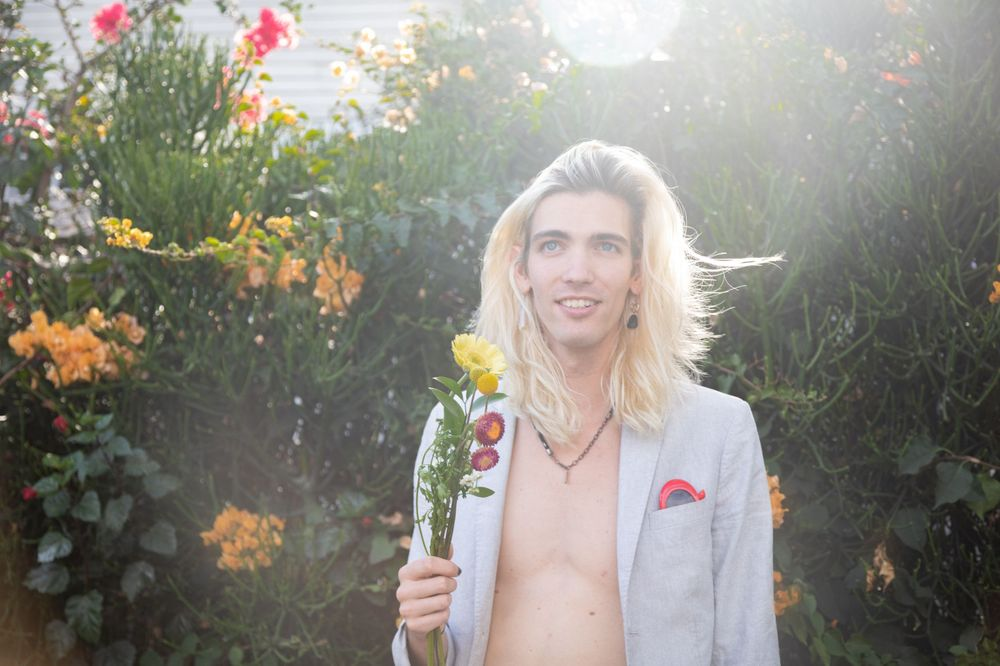 Musician Clark Hawkes holding flowers in Hollywood