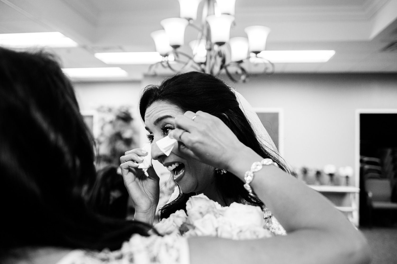Bride wipes away tears after wedding ceremony