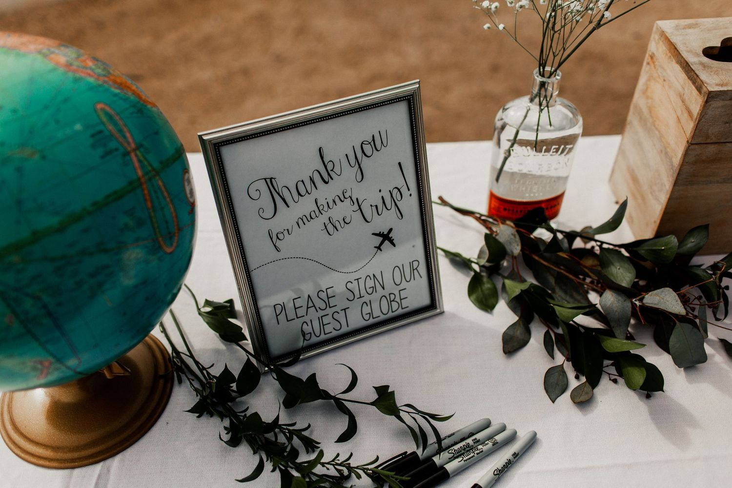 reception decor and sign in with globe at wedding reception