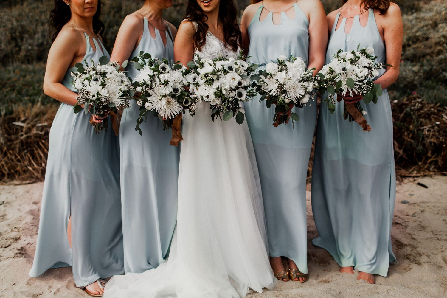 bridesmaids with blue dress and bridal party with flowers