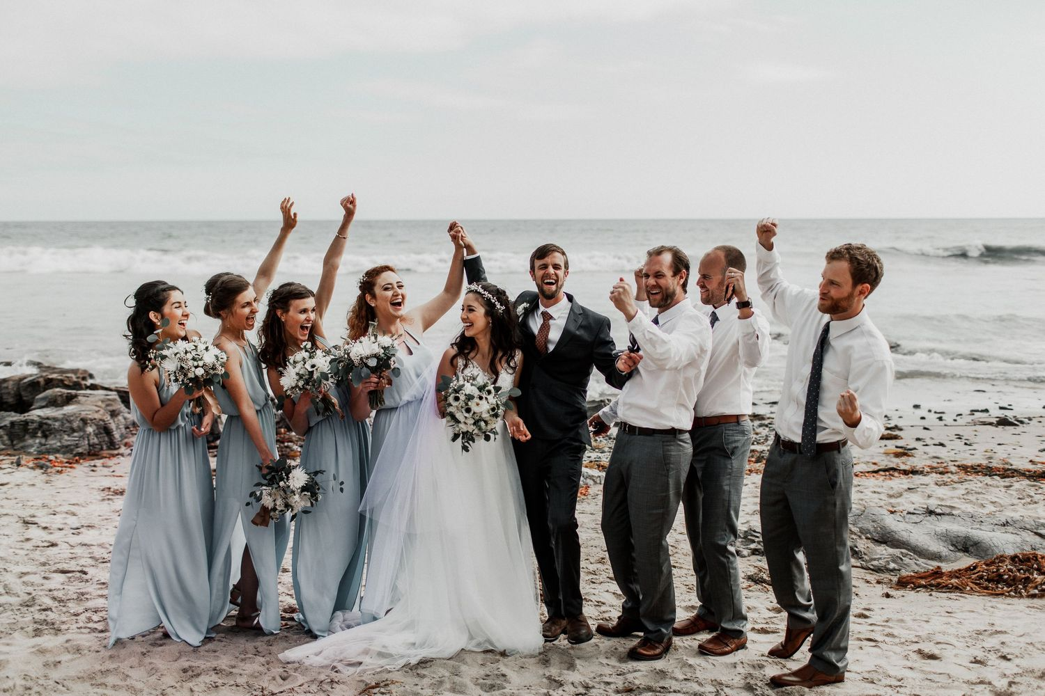 bridal party cheering on bride and groom at crystal cove beach