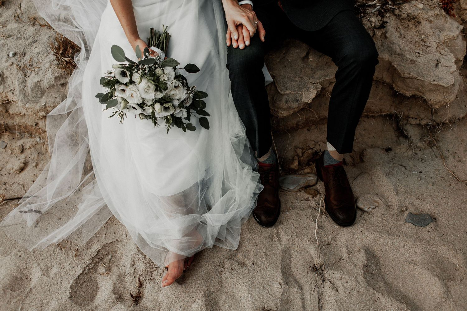 bride and groom sitting on a log with bouquet and details